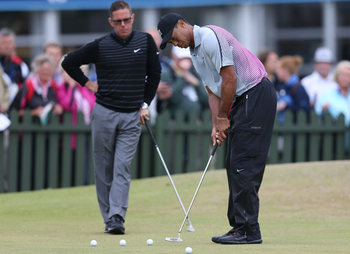 Tiger Woods works on the practice green alongside coach Sean Foley.