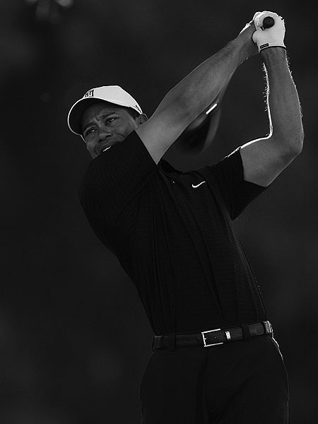 """Here is an image that evokes those of yesteryear. And not just because it is in black and white. Tiger's form-fitting shirt highlights his torso and biceps just like those old tighties Arnie, Jack and Gary blew away the ladies with. Subtly macho. The power stroke is emphasized by the blur of his clubhead. The tiny bit of sunlight through the trees behind him details the muscles in his arms. Again, a very classic pose from a very modern champion."""