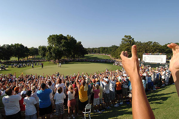"""During this year's PGA Championship at Southern Hills in Tulsa, I planned to hang a remote camera at the 18th hole, but changed my mind and shot wide from the 10th tee box. I was quite pleased with this photo until I noticed the frame included the clapping hands of the fan who was next to me. The editors back in New York were quite pleased, however, with his hands, which perfectly framed the scoreboard."""