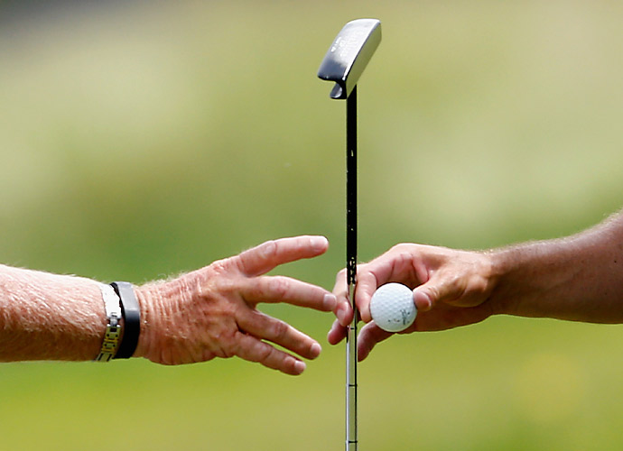 Zach Johnson hands his putter and golf ball to his caddie on Thursday.