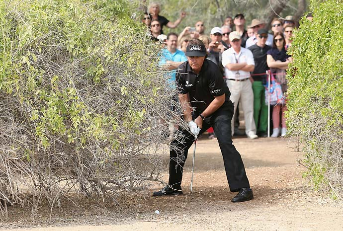 Phil Mickelson plays right-handed from under a bush on the 13th hole, double-hitting the ball in the process, during the final round of the Abu Dhabi HSBC Golf Championship.