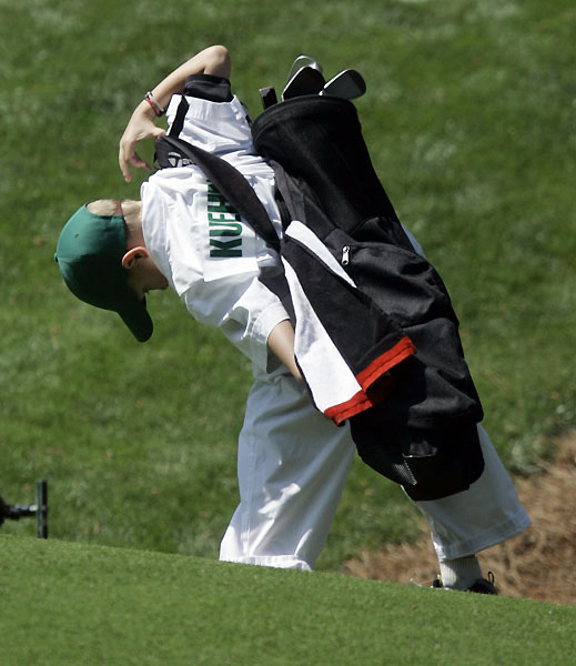 Trip Kuehne's son struggled to get his dad's golf bag on his back.
