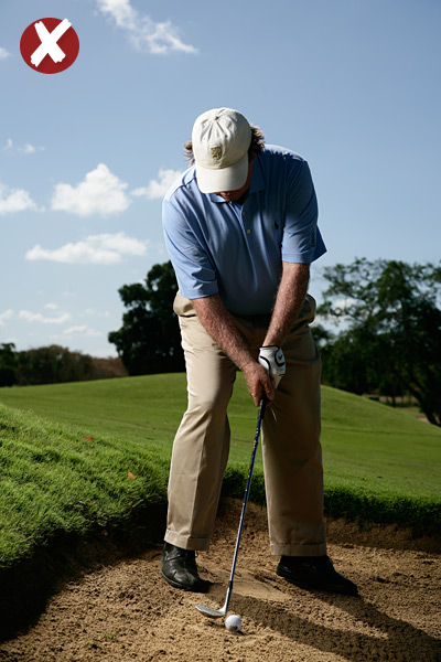 STEP 2                                              Make a few practice backswings (without touching the sand) to make sure you clear the lip. Keep in mind that your body is tilted with the hill—make sure your swing does the same. A good thing to think about is moving your left-hand knuckles down the hill on your way back to the ball. Since you've adjusted your body to the slope, the ball should pop out like a regular bunker shot.
