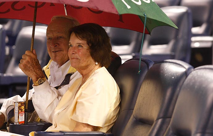 Arnold Palmer sits under an umbrella with his wife Kathleen Gawthrop during a rain delay of a game between the Pittsburgh Pirates and the Cincinnati Reds on July 18, 2011 at PNC Park in Pittsburgh.