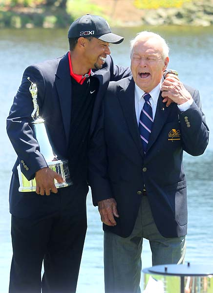 Tiger Woods shares a laugh with Arnold Palmer as Woods holds the Arnold Palmer Invitational trophy after winning the Arnold Palmer Invitational at Bay Hill Club & Lodge in Orlando, Fla., in March 2013