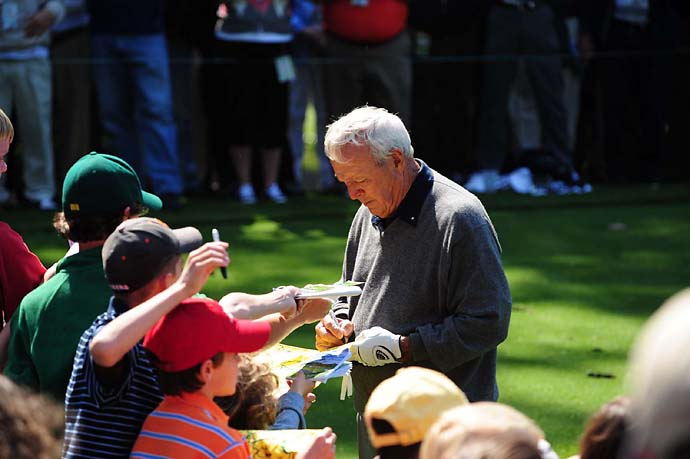 Arnold Palmer signs autographs during the Par 3 Contest at the 2009 Masters.