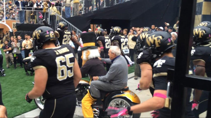 @coribritt: #ArnoldPalmer rode the motorcycle out to start the @wakefb game today.  He's driving it next time.