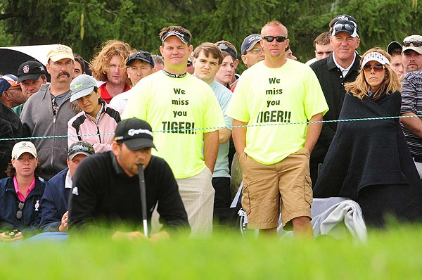 "Even when Tiger Woods is not at the tournament, his presence can be felt. Here some spectators sported ""We miss you Tiger"" shirts as Garcia putted."