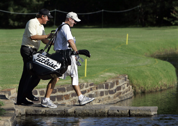 Phil Mickelson, left, jokingly helped Davis Love III's caddie Joe LaCava across a foot bridge at the sixth hole.