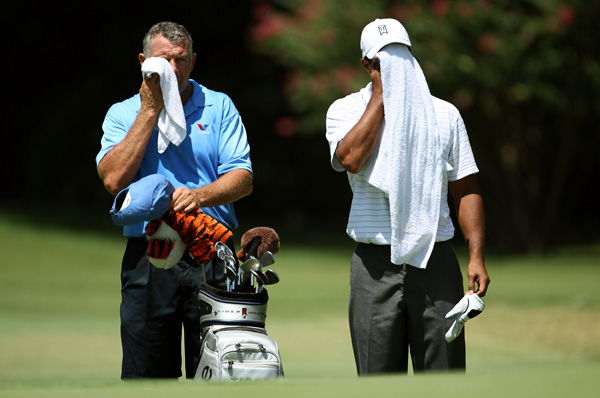 Woods and his caddie, Steve Williams, tried to stay cool in the Tulsa heat. A heat warning is in effect through Sunday as temperatures are expected to be above 100 degrees.