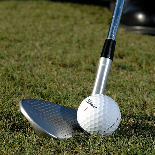 HOW TO DO IT                                              STEP 1                                              Grab your sand wedge and open the face a few degrees — you'll need the extra loft to control your carry distance with a fast swing.
