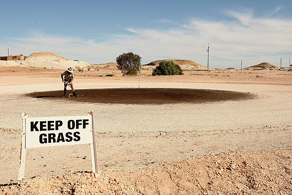 "A local rakes out the green at the grassless Coober Pedy Golf Course in Australia. The ""greens"" are oiled to keep the sand from blowing away."