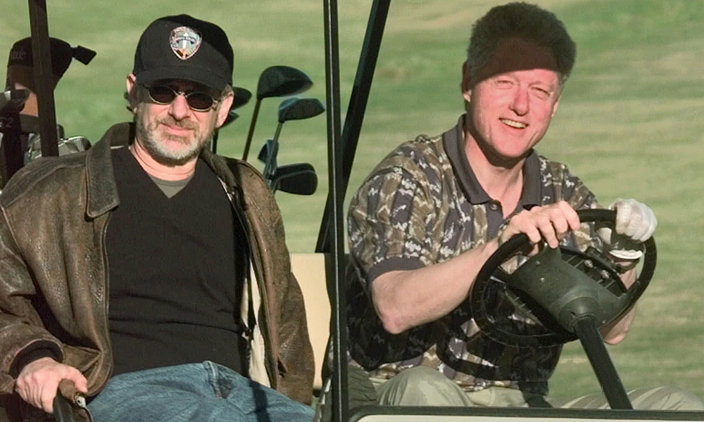 Clinton with Steven Spielberg, dressed more for directing than swinging, at Maple Run Golf Course in Maryland in 1998.