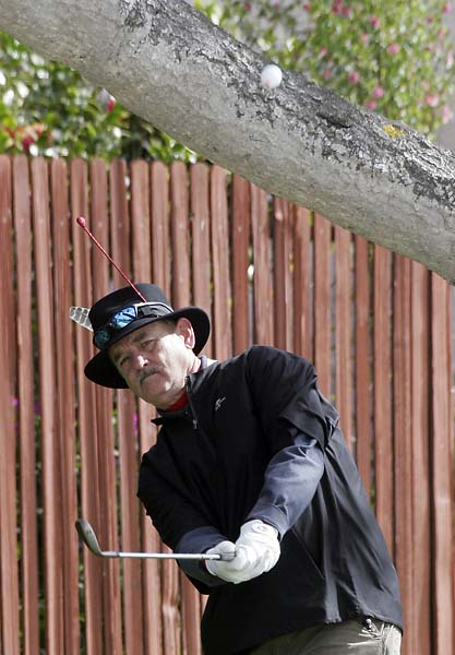 Bill Murray hits a chip shot under a tree trunk on the 14th hole during the third round of the 2009 Pebble Beach National Pro-Am.