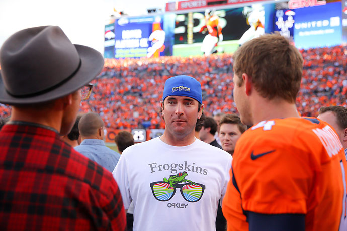 Bubba Watson has a word with Broncos punter Britton Colquitt before a game between the Denver Broncos and the Indianapolis Colts at Mile High Stadium following the BMW Championship at Cherry Hills.