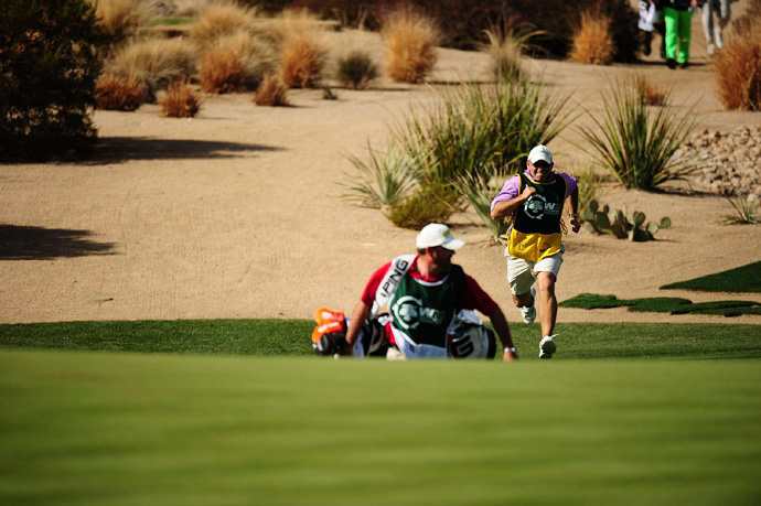 A new tradition has started at the par-3 16th -- caddies race from the tee to the green.