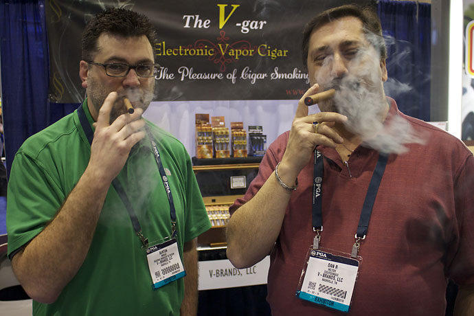 Burton Brooks, left, and Dan R. Helton enjoy a completely legal electonic cigar at the PGA Show on Thursday. Helton says he quit a 20-year cigar habit and only smokes e-cigars now. For more information, visit V-gar.com.
