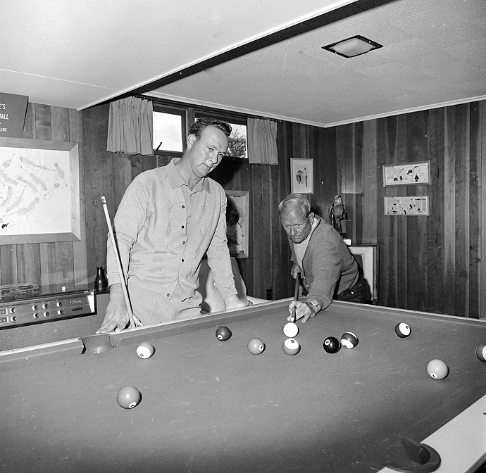 "Arnold Palmer tests his eye at the pool table at his Latrobe, Pa., home with his father, W.J. ""Deacon"" Palmer on April 15, 1964."