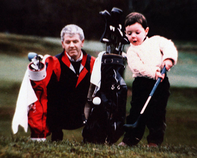An 18-month-old Rory McIlroy plays golf with his father Gerry watching.