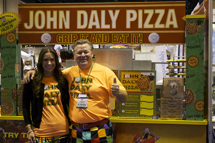 "Alison Skipper and Jimmy Howell serve John Daly Pizza -- ""Grip it and eat it!"" -- to hungry PGA Show attendees on Thursday. For more information, visit JohnDalyPizza.com."