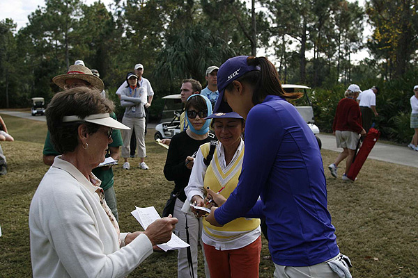 Wie has declined to give any interviews after rounds, but stops to sign autographs for fans.