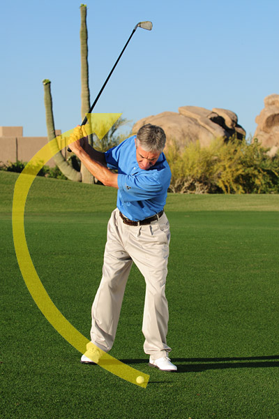 Step 2: Take the club back along the slope. Since the ground behind the ball is higher than the ground in front of it, your backswing will be much steeper. Fight the urge to strand weight on your left foot.