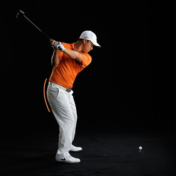 AT THE TOP: I'm coiled and in control. Then, to start my downswing...