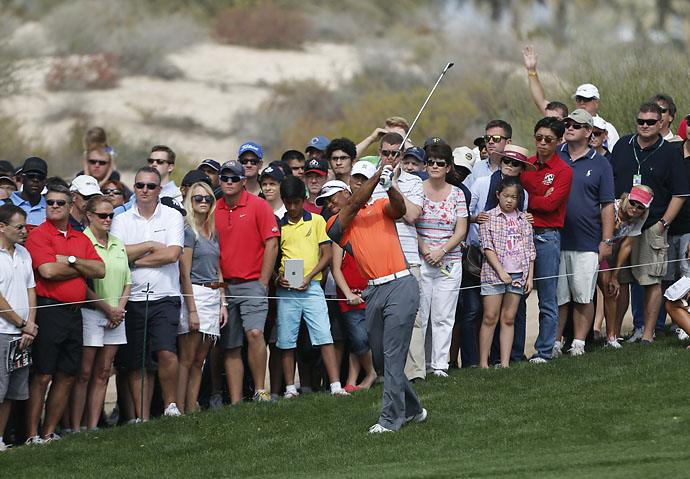 Tiger Woods hits a shot in front of the audience during the third round of the 2014 Omega Dubai Desert Classic.