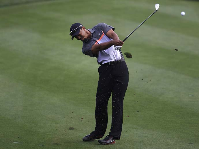 Tiger Woods plays a ball on the 14th hole during the first round of the Dubai Desert Classic golf tournament in Dubai, United Arab Emirates, Thursday, Jan. 30, 2014.
