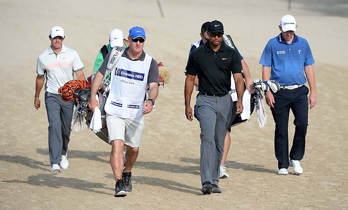 Rory McIlroy, Tiger Woods, and Stephen Gallacher walk with their caddies on the 14th hole during the second round of the Omega Dubai Desert.