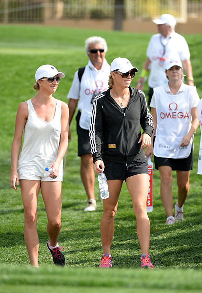 Caroline Wozniacki and an unidentified friend walk with Rory McIlroy's group during the third round of the 2014 Omega Dubai Desert Classic.