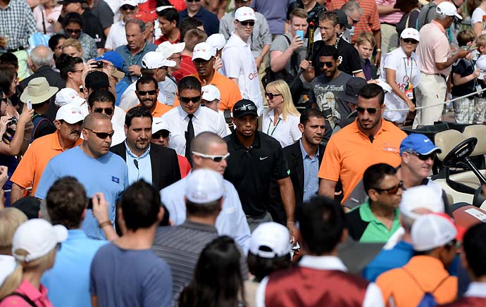 Tiger Woods makes his way through the crowds on his way to the first tee during the second round of the Omega Dubai Desert Classic.