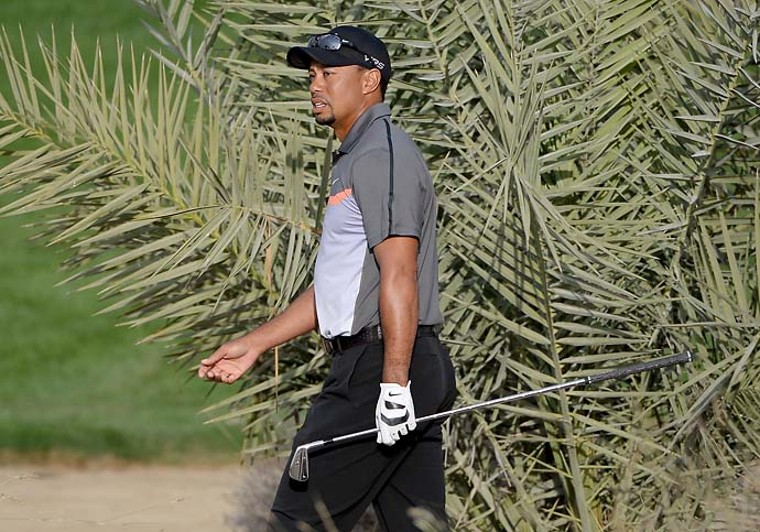 "Tiger Woods plays his second shot on the 10th hole during the first round of the Dubai Desert Classic. ""I'm going to work on a couple of things here and there but I felt like it was a good day,"" Woods said after shooting 68."
