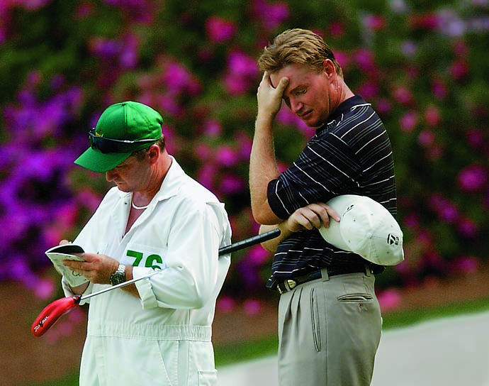 Ernie Els stands on the 13th green with his caddie, Ricci Roberts, after having trouble getting to the green by hitting into the woods on the hole during the final round of the 2002 Masters.