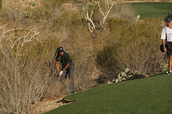 After a wayward drive, Woods lost the match when he needed two shots to get out of the desert.