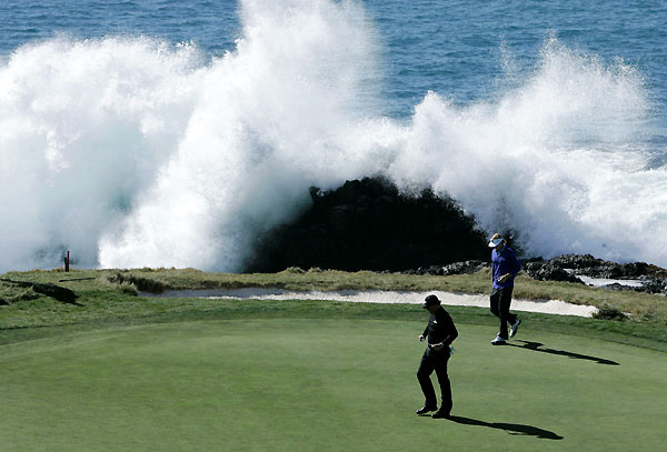 Waves crashed on the scenic seventh hole at Pebble Beach as Mickelson, center, and Brandt Snedeker lined up their putts.