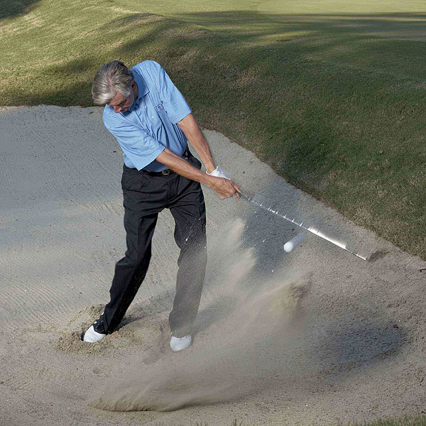 3. When you set up for your bunker shot, dig your toes into the sand. This lets your swing naturally bottom out under the ball. Don't worry about hitting a precise spot behind the ball—you can hit anywhere from 2-4 inches back. As long as the tee in your club points at your target, your ball will explode out and reach the green.