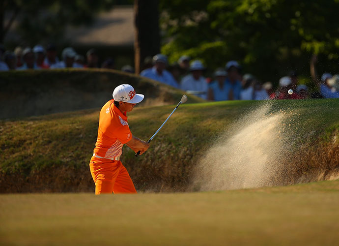 Fowler chips out a bunker. His bid to overtake Kaymer ended on the fourth hole. He sent his third shot over the green and into some pine trees. He had to drain a 25-foot putt just to save double bogey.