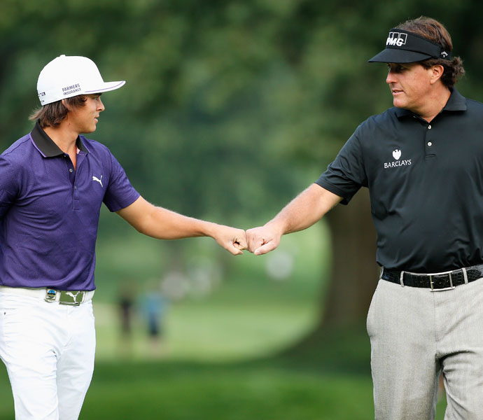 Phil Mickelson and Rickie Fowler fist-bump their way down the course during practice at Oak Hill.