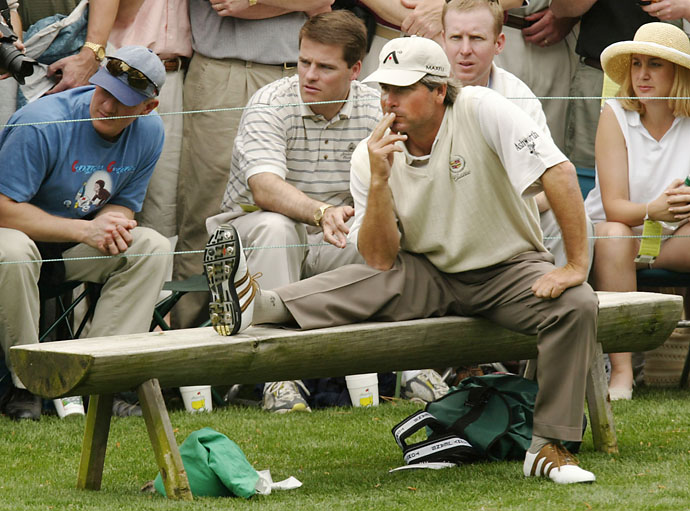 Fred Couples waits on a bench at the 16th tee during his practice round at the 2002 Masters.