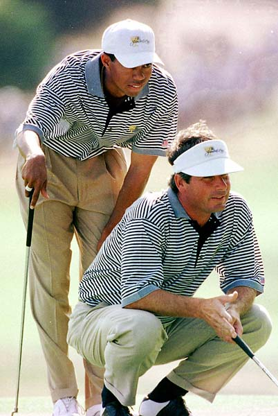 Fred Couples and Tiger Woods line up a putt in a Presidents Cup match against the International pairing of Craig Parry and Shigeki Maruyama during the second day morning foursomes at Royal Melbourne Golf Course in December 1998.