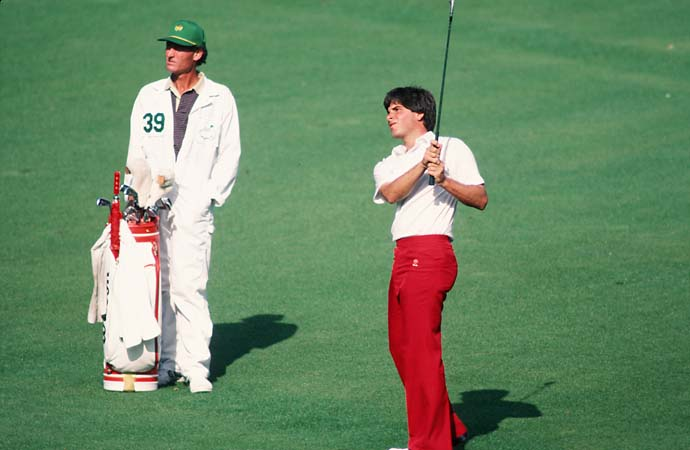 Fred Couples watches his shot off the fairway next to his caddie during the 1984 Masters.