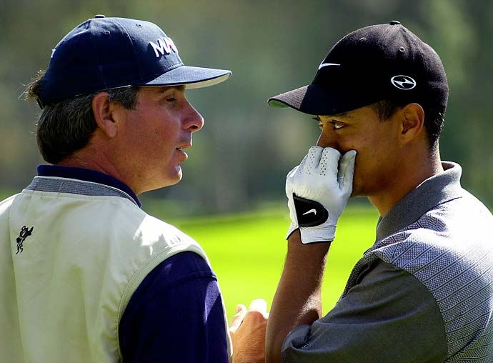 Tiger Woods shares a private word with Fred Couples on the driving range following a practice round for the upcoming Nissan Open at Riviera Country Club on Feb. 21, 2001, in Los Angeles.