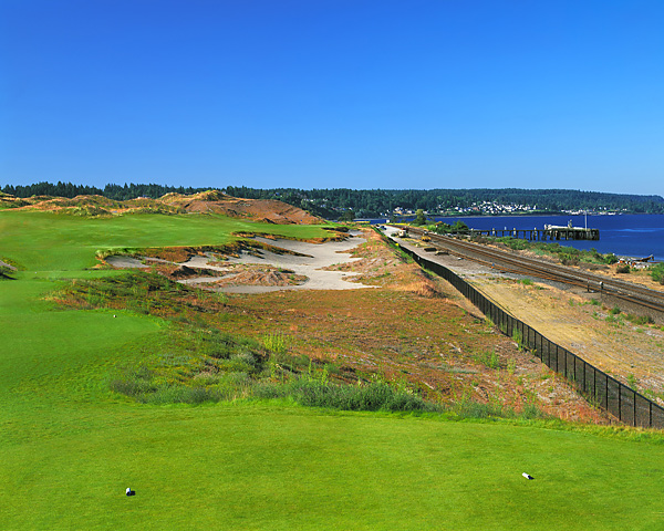 This hole is flexible in length and can be played as a drivable par 4. Golf shots are played along the railroad tracks across and between vast sandy wastelands. It is a beautiful, relatively flat golf hole, where all shot options are apparent. The strong player can take dead aim at the green. However, any mistake will be severely punished. Play safe and you still have a very small target green to approach from an awkward angle. Note the tire marks from the tractors in the right of the photo. This shot was taken early in the course's life when much of the grass outside of the fairways had yet to grow in. We left the tire contours specifically to give the grass seeds a place to find purchase in the windy and sometimes rainy conditions. This created a very natural pattern of growth.