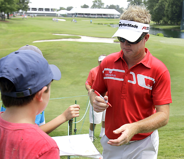 Defending champion Brian Gay signed a few autographs after opening with a three-over 73.