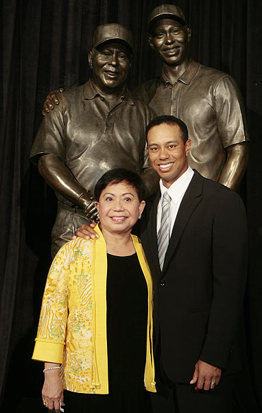 Woods with his mother, Kultilda, in front of the 8-foot bronze statue, which will remain in the lobby of the learning center.