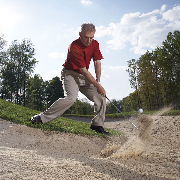 How to Blast One From Below Your Feet                       Your knees are the key to digging the ball out                                              By Steve Bosdosh                       Top 100 Teacher                                              This story is for you if...                       • You have trouble with normal lies in a                       bunker and...                       • ...you feel as if you have no chance when                       the ball is below your feet.                                                                     The Situation                       With your ball in the sand,                       you're forced to stand outside                       the bunker to take your                       stance, and the ball is well                       below your feet.                                              The Solution                       You'll need extra bend in your                       knees at address in order to                       get your club down to the ball.                       More important, they'll have to                       remain bent during your swing                       or you'll catch the top half of                       the ball. Control your knees                       and this becomes a relatively                       simple bunker shot.