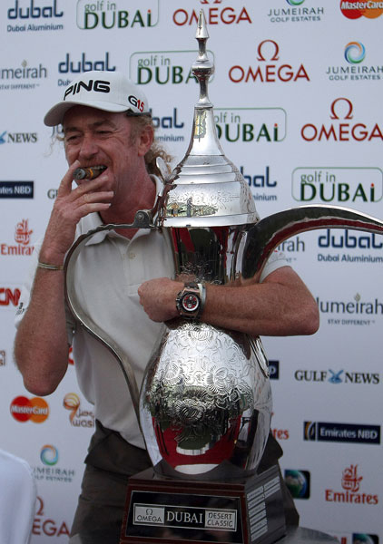Miguel Angel Jimenez hugs his 2010 Dubai Desert Classic trophy while polishing off another victory cigar. The Spaniard defeated Lee Westwood on the third hole of a playoff.