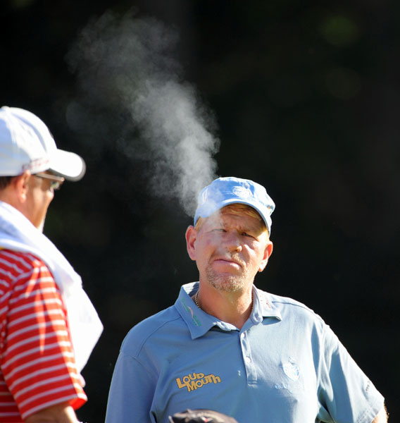 A slimmed-down John Daly exhales cigarette smoke before hitting a tee shot during the first round of the 2011 PGA Championship at the Atlanta Athletic Club. Daly (77-76) missed the cut.