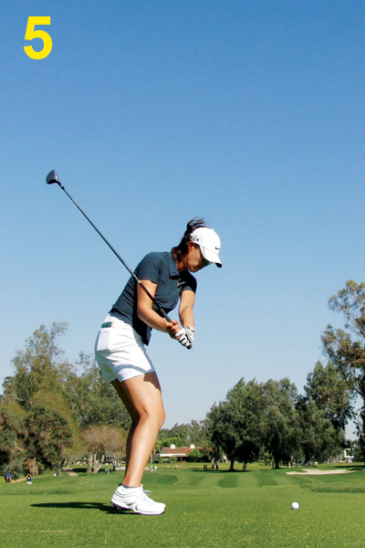 5. Halfway down, Michelle's arms and clubshaft are in an ideal position. The shaft points right at the ball, and her spine has lowered into the delivery position. The clubface looks vertical and square as it should on a fairway wood or driver.